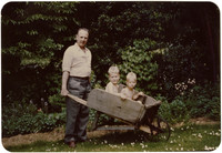 Two boys in a wheelbarrow pushed by a man