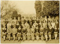 Thirty nine teenage girls pose in three rows outdoors near an ivy-covered building.