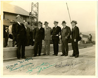 Several men in suits and hats, and one man in ship captain's uniform, pose on dock with warehouse and water in background