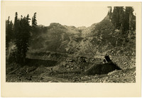 Broad view of road construction along mountainside
