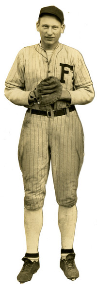 "Man poses in baseball uniform with glove and ""F"" on his uniform."