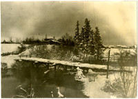 A simple bridge with no railing spans a creek in a snowy, wintertime scene