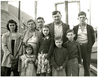 "The Satko family of 9 stand somberly on dock with their ""Ark of Juneau"" boat in background"