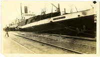 """Pacific American Fisheries transport ship """"Firwood"""" loaded with pilings, anchored at unidentified pier"""