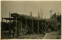 Hull of large vessel under construction beachside