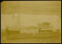 Five men pose atop the roof of a sternwheel-powered river barge