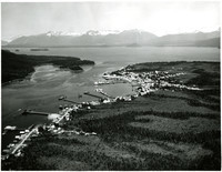 Aerial view of waterfront town of Petersburg, Alaska, on Frederick Sound with snow-capped mountains in distance