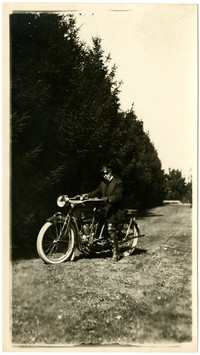 A policeman stands astride his motorcycle