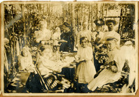 Picnic scene in the woods with women, men and children around a table