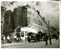 Fire engines with hoses and ladders fight structure fire as it billows smoke, with people watching from street below