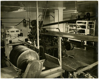 Room with unidentified large machinery possibly used for fish processing or canning