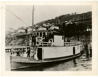 "About a dozen men, women, children on decks of small steamer ""Brick"" docked at pier below steep hill"