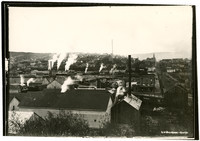 Easterly view from lower part of Harris avenue of early Fairhaven, WA, with industrial port buildings in foreground, Fairhaven Hotel in distance