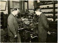 Two mechanics in machine shop using a metal lathe