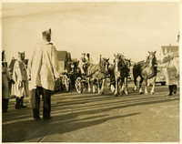 Several men apparently dressed in fraternal order garb watch a buggy driver struggle to lead a team of four horses