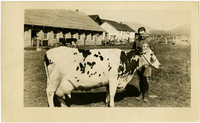 Man poses behind large Holstein dairy cow with barns and corrals in background