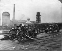Lumber Mill, Station #2 - Two old fashioned fire trucks with hoses outstretched on a plank roadway.