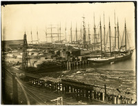 Masted freight vessels are moored to dock covered with piles of cut lumber, with logs floating in bay adjacent
