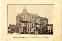 """Four-story sandstone """"Lighthouse Building"""" in downtown Bellingham, WA, with multi-faceted clocktower and street-level businesses"""