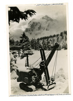 Snowy scene of Mt. Shuksan and surrounding forest with snowcat machine in foreground