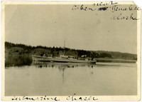 A submarine chaser travels in calm waters near Tanakee, Alaska, with forested shoreline in background