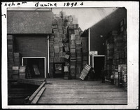 A huge pile of wooden crates piled high with five men perched among the crates all the way to the roof of the adjacent building where there is a sign that says
