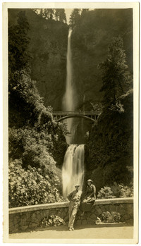 A woman sits on the the roadslide stone wall with a man next to her, with Multnomah Falls in background