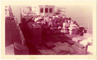 Deck of unidentified ship at dock, loaded with supplies in boxes, sacks, metal containers
