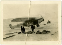 """Fokker prop plane with """"Detroit Arctic Expedition , G.H. Wilkins, Commander"""" written on its side, parked on ice field with three heavily-clad people standing beside it  with their gear strewn nearby"""
