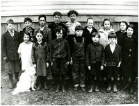 Young school children and a teacher pose in two rows outside schoolhouse