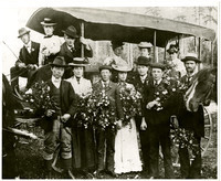 Thirteen students and teachers of Fairhaven high school class of 1900, sitting in and standing next to a horse drawn carriage, holding bouquets of flowers