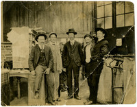 Five men stand among sorting boxes and canvas bags in post office