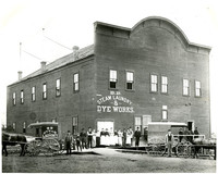 Men and women workers, and two horse-drawn delivery buggies, stand in front of large warehouse of B.B. Steam Laundry & Dye Works
