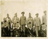 Twelve older men in military uniforms standing in two rows