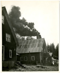 Several unidentified industrial buildings  with smoke billowing from three smoke stacks in background