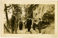 Four men in suits and three workmen stand on rocky hilside path