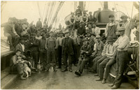 Diverse crew of fishermen stand on deck of steam-sail vessel