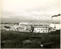Waterfront industrial complex with railroad in foreground