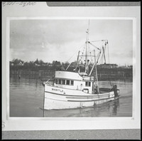 "The fishing boat ""Martle"" in Bellingham Bay heading out from shore with Eldridge Avenue in the background"