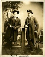 Two men pose against fence in studio portrait