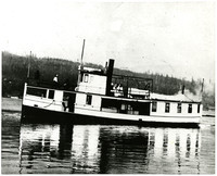 Steamer ferry in calm waters with several people on top deck, forested hills in background