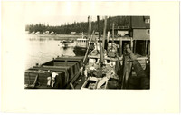 Workers on deck of fishing tender moored Kassan cannery docks with seaplane on water in background