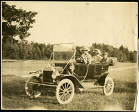 Two women and a boy sit in an early model car in a grassy clearing