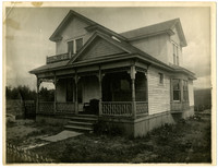 Front exterior of house with porch, grass-less yard, and picket fence