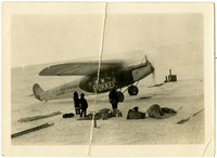 "Fokker prop plane with ""Detroit Arctic Expedition , G.H. Wilkins, Commander"" written on its side, parked on ice field with three heavily-clad people standing beside it  with their gear strewn nearby"