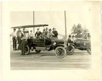 Ten men pose on a Burlington Fire Department hook and ladder motorized truck, with two men sitting in a racing car on right