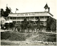 Several people wander along boardwalk in front of Hotel de Haro, Roche Harbor, San Juan Island