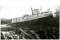 """Lake Whatcom steamer """"Marguerite"""" completely out of the water on shoreline with floating logs in foreground"""