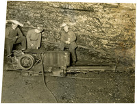 Three miners with lighted helmets pose next to coal extraction equipment in mine