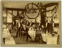 Formally dressed African-American waitstaff pose in Fairhaven Hotel dining room with Christmas decorations